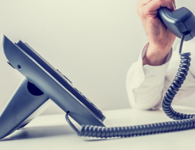 Mann nimmt Anruf entgegen und zeigt Erreichbarkeit mit Verkaufspsychologie