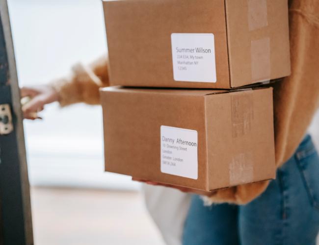 Frau nimmt Pakete entgegen - Kunden wollen auf Versandkosten verzichten